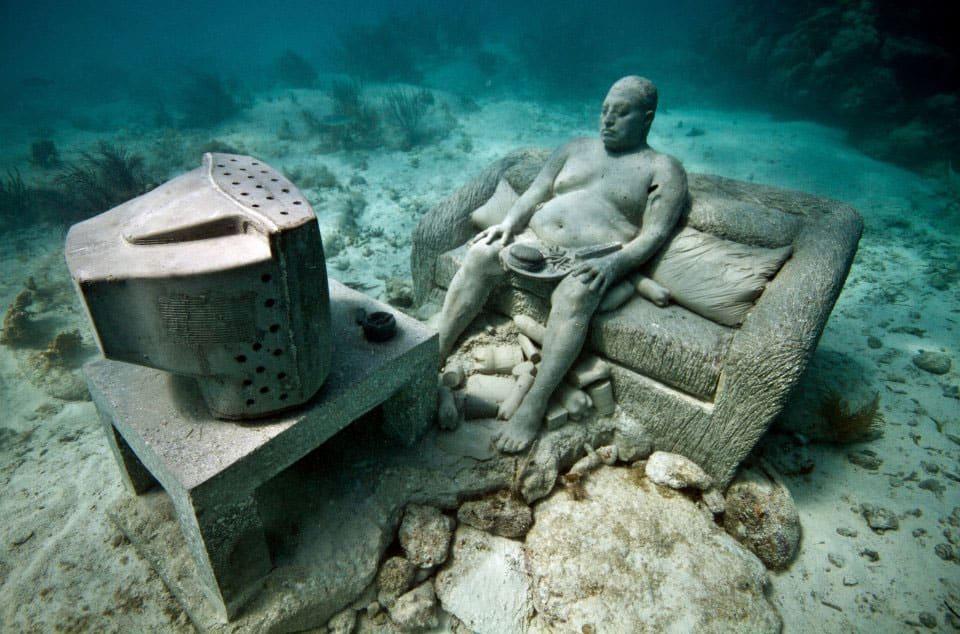"""""""Inércia"""" mostra um homem obeso e sedentário em um sofá assistindo televisão, ignorante da nossa crise ambiental; no entanto, a escultura da televisão oferece um espaço de habitat para filhotes de peixes"""