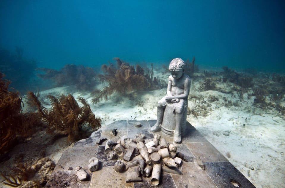 """""""Herança"""" mostra um menino contemplando objetos retirados do mar e que causam a sua poluição – uma herança indesejada"""