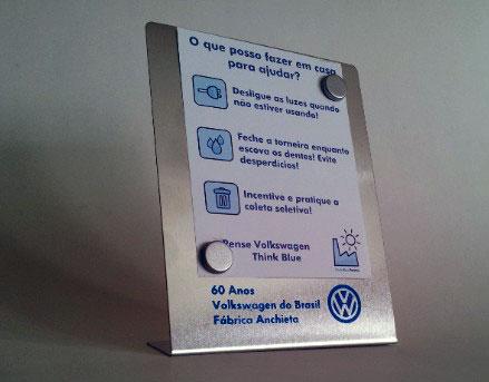 O brinde especial do evento: uma placa para recados - com dois ímãs para segurar a mensagem ou foto; a forma lembra um troféuzinho e a inscrição diz: 60 Anos - Volkswagen no Brasil - Fábrica Anchieta