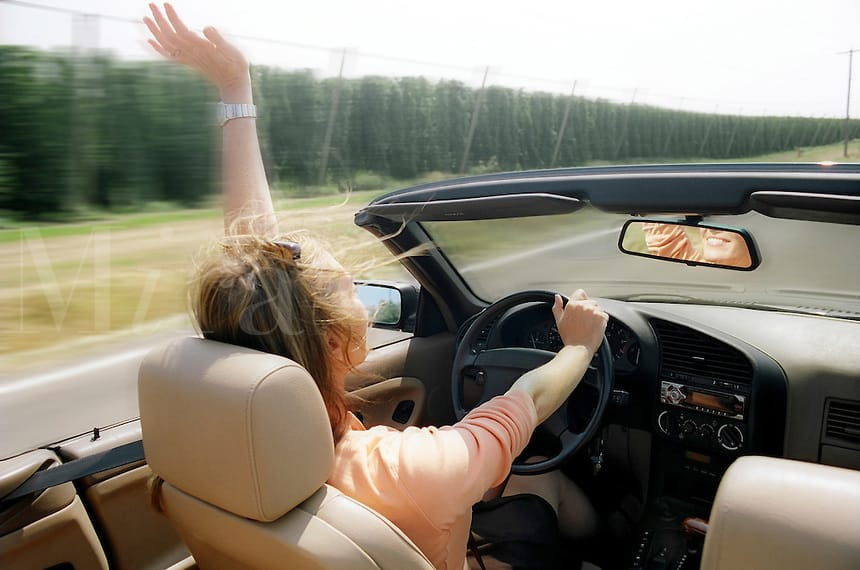 Woman driving convertible through the countryside. MR
