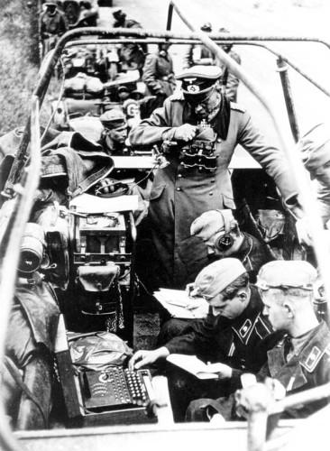 De cima para baixo, general de divisão Panzer, radio-telegrafista e operadores de máquina ENIGMA trabalhando na carroceria de um caminhão.