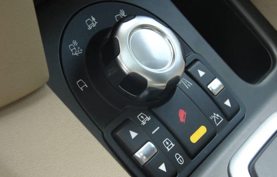 Painel de Comandos de um Land Rover Discovery 4. É possível ver em sentido horário, a partir do canto esquerdo inferior: posição da suspensão pneumática, seletor de terrenos, acionamento reduzida ou normal e HDC. Foto: UOL Carplace