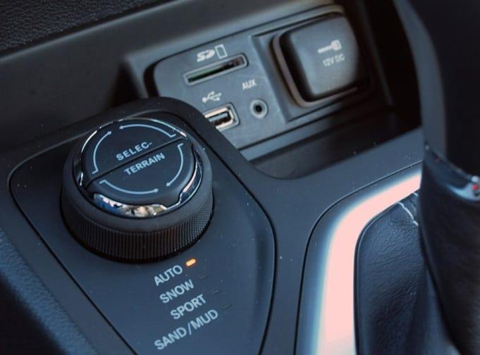 O comando da tração, entradas USB, auxiliar e cartão SD. Tomada de energia com tampa